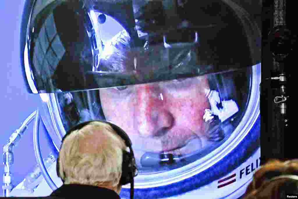 Baumgartner is seen inside the capsule on a screen at mission control during the final moments of the ascent.