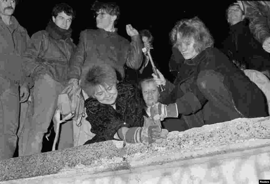 Berliners take a hammer and chisel to a section of the Berlin Wall in front of the Brandenburg Gate after the opening of the East German border was announced on November 9, 1989.
