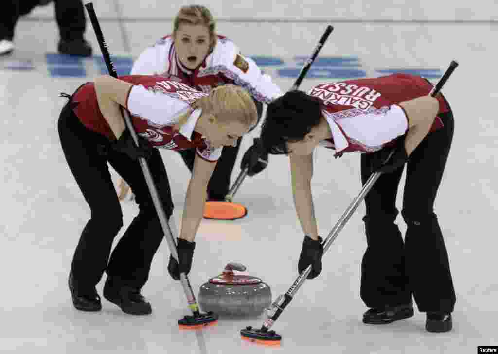 Russia'san curlers Alexandra Saitova (left) and Ekaterina Galkina (right) sweep furiously ahead of teammate Margarita Fomina during their women's curling round robin game against the United States.