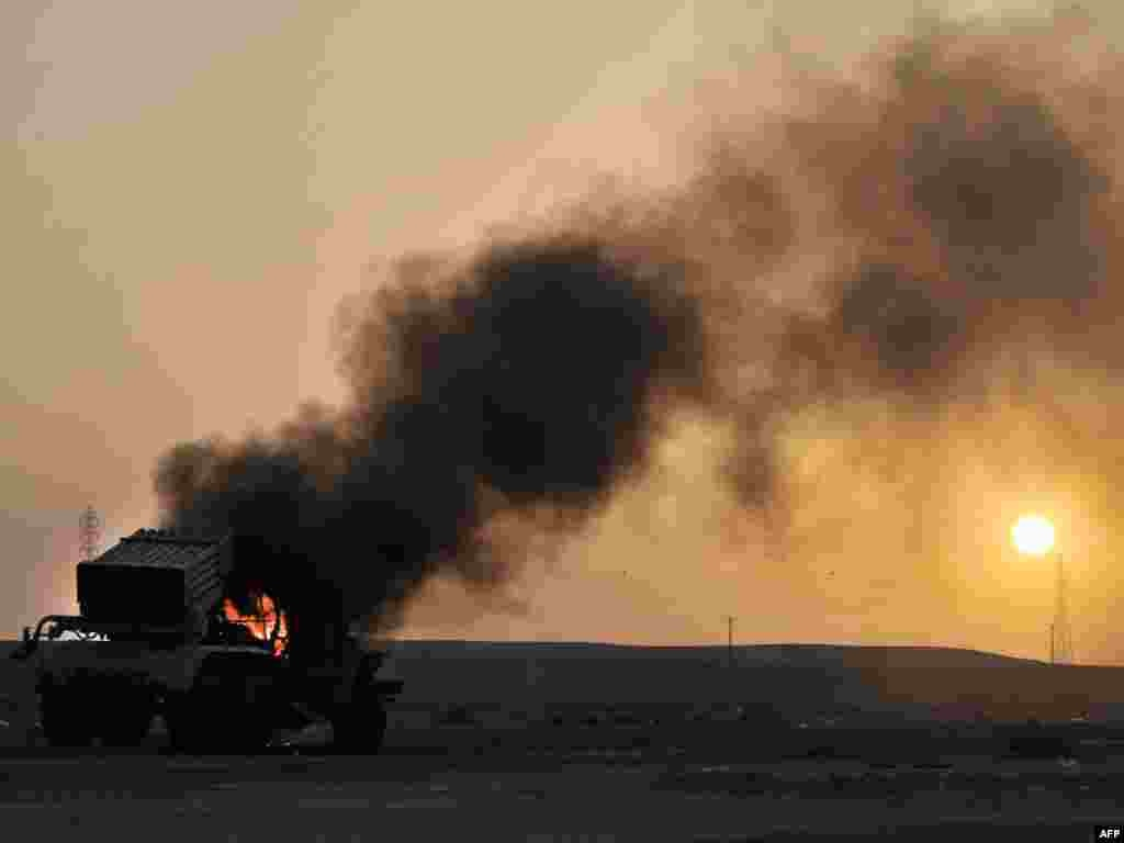 A multirocket launcher burns at sunset outside the oil-rich town of Ras Lanuf on March 27 as rebels press on as far as Nofilia with Muammar Qaddafi's hometown of Sirte, 360 kilometers east of the capital, Tripoli, in their sights. Photo by Aris Messinis for AFP