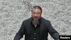 "Chinese artist Ai Weiwei throws porcelain sunflower seeds into the air as he poses with his ""Sunflower Seeds"" installation in the Turbine Hall at the Tate Modern art gallery in London in October 2010."