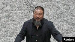 """Ai Weiwei cu """"Sunflower Seeds"""", lucrarea sa expusă la Tate Modern Gallery, la London, în octombrie 2010"""