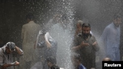 People cool off in spray from a leaking pipe during Karachi's 2015 heat wave.