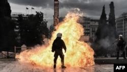 Выбух бутэлькі з запальнай сумесьсю каля паліцыянта падчас пратэсту ў Атэнах 4 лютага.