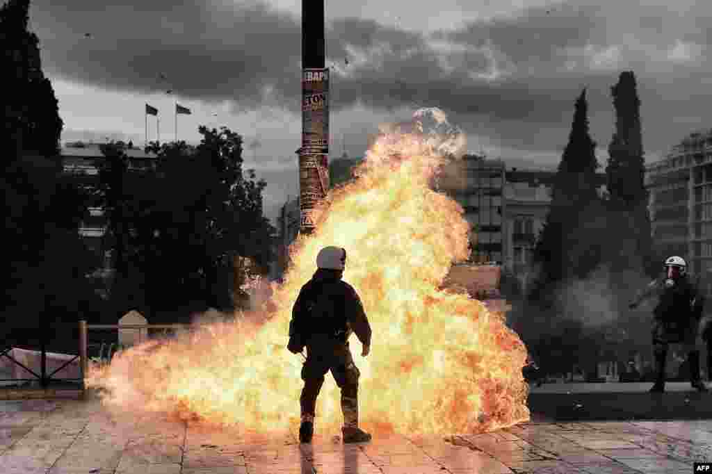 A firebomb explodes beside a riot policeman during a massive protest in Athens on February 4. (AFP/Aris Messinis)