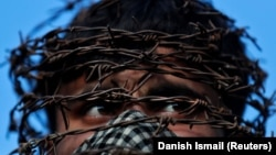 A masked Kashmiri man with his head covered with barbed wire attends a protest in Srinagar on October 11.