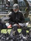ROMANIA - A man rests on bench after feeding pigeons in Bucharest, Romania, March 27, 2020