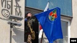Один из протестующих, оккупирующих правительственное здание в Луганске, устанавливает на нем флаг. 9 апреля 2014 года.