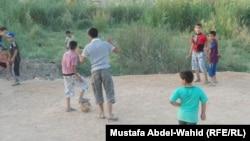 أطفال يلعبون كرة قدم في ساحة بكربلاء