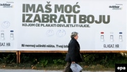 Сайлауға дауыс беруге шақырған билбордтың қасынан өтіп бара жатқан әйел. Загреб, 4 қараша 2015 жыл.