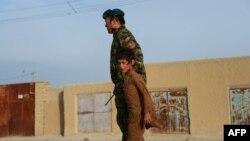 Një fëmijë dhe një ushtar afgan, foto nga arkivi