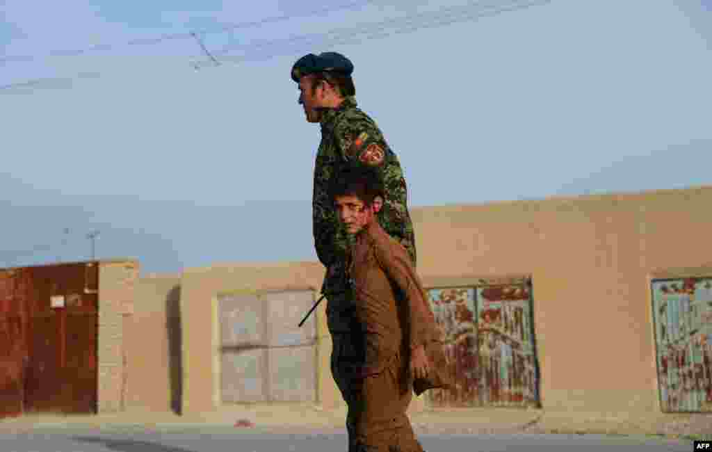 A wounded Afghan boy walks with a soldier at the site of a suicide attack near Mazar-e Sharif, on February 8. (AFP/Farshad Usyan)