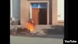 """Совершивший самоподжог молодой человек вбегает в здание регионального филиала партии """"Нур Отан""""."""