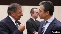 U.S. Secretary of Defense Leon Panetta (left) talks to NATO Secretary-General Anders Fogh Rasmussen during a NATO defense ministers meeting in Brussels on October 10.