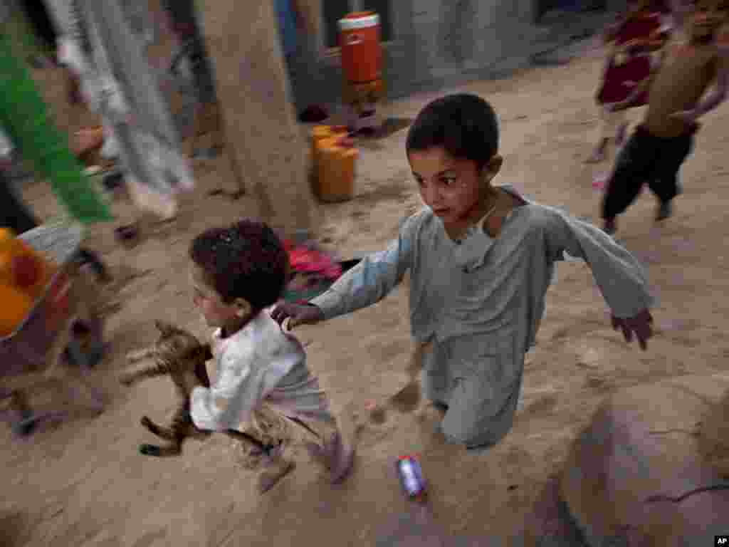 Riyaz Ahmed (left), an internally displaced Afghan boy, runs away with a kitten he caught near his impoverished house at a refugee camp in Kabul, Afghanistan, on August 9. According to UN, some 2.7 million registered Afghans refugees remain in Pakistan and Iran.Photo by Dar Yasin for AP