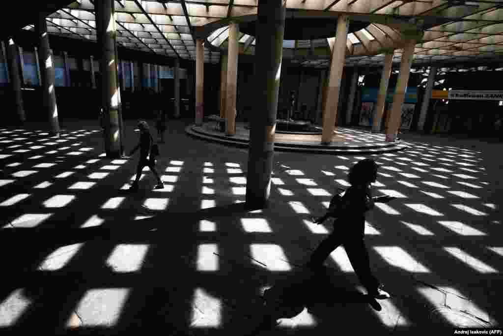 People walk through a passageway on a sunny day in the Serbian capital, Belgrade. (AFP/Andrej Isakovic)