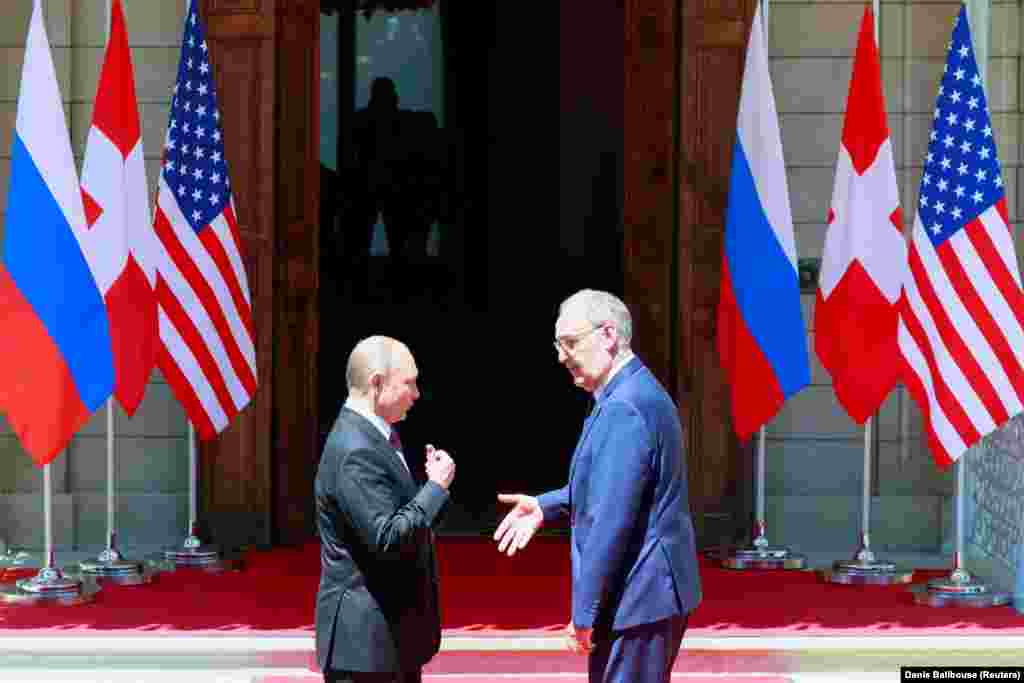 Президент Швейцарии Ги Пармелен приветствует президента России Владимира Путина перед тем, как войти на виллу.