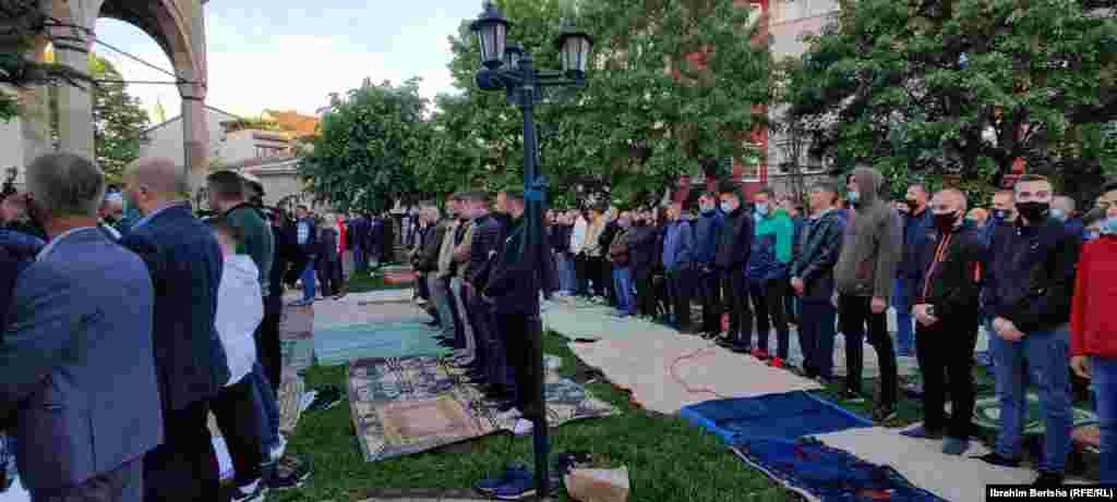 Musulmanlar Priştinanıñ esas camisi yanında, Kosovo
