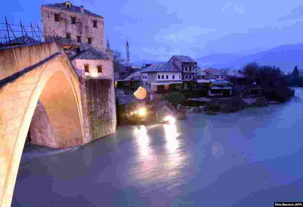 The historic bridge in Mostar, Bosnia, is seen after the level of the Neretva River rose approximately three meters compared to its normal levels. Water levels have dramaticaly risen countrywide due to snow melt and large quantities of rain in the past week. (AFP/Elvis Barukcic)