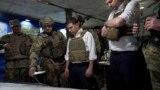 UKRAINE -- Ukrainian President Volodymyr Zelenskiy, center, listens to a serviceman as he visits the war-hit Donetsk region, October 14, 2019