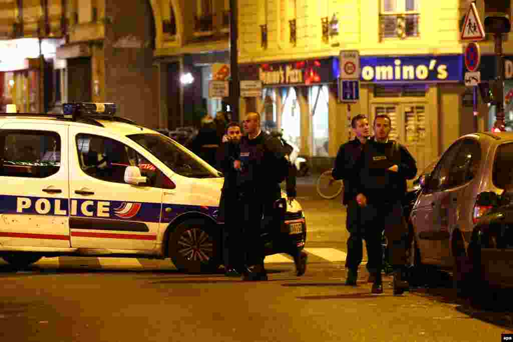 Police officers arrive at the scene of one of the fatal shootings in Paris on November 13.