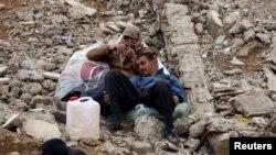 دو تن از شهروندان غیرنظامی موصل که موفق به خروج از محل درگیریها شدهاند در انتظار کسب اجازه ورود به اردوگاه آوارگان هستند