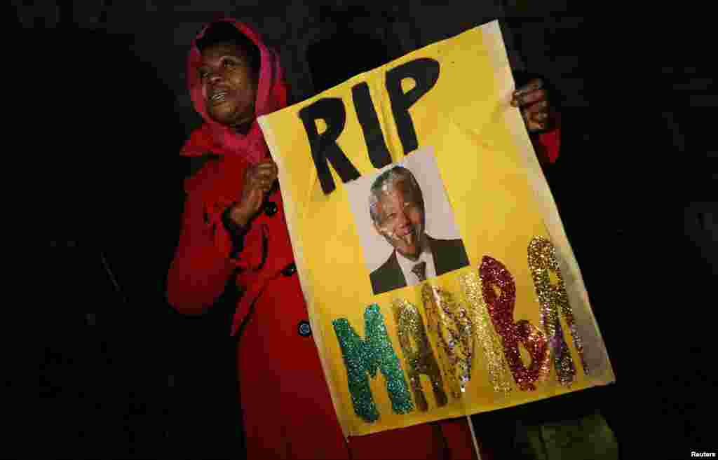 A woman holds a sign at a gathering in memory of Nelson Mandela outside the South African High Commission across from Trafalgar Square in London. (Reuters/Suzanne Plunkett)