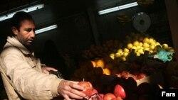 میوه فروش تهرانی در حال مرتب کردن انارهای شب یلدا