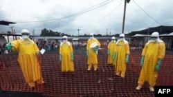 Медики в специальных защитных костюмах в зоне, где зафиксирована эпидемия Эболы.