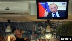 Мужчина смотрит телевизор, по которому транслируют пресс-конференцию президента России Владимира Путина. Киев, 4 марта 2014 года.