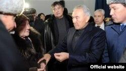 Президент Казахстана Нурсултан Назарбаев говорит с жительницей города Жанаозен. 22 декабря 2011 года.