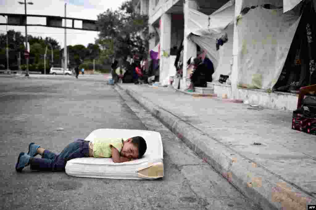 A refugee boy rests in a makeshift camp situated at the old Athens airport. The Greek asylum service launched the registration of the migrants inside some of the camps in an attempt to speed up the asylum process. (AFP/Louisa Gouliamaki)