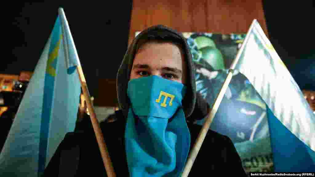 Учасник акції з кримськотатарським прапором і символікою
