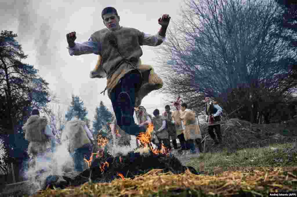 Serbia, March 1: A boy leaps over a fire during a traditional carnival in the village of Lozovik, near Belgrade. Five days after this photo was taken, Serbia reported its first case of COVID-19 in a man who had recently returned from Budapest. Two have died from the virus in Serbia as of March 23.
