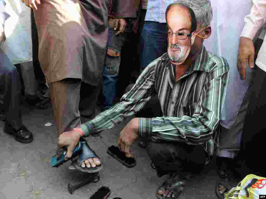 A cobbler wearing a Rushdie mask polishes shoes outside a mosque during a protest by an Islamic organization in Mumbai, India, in January 2012.