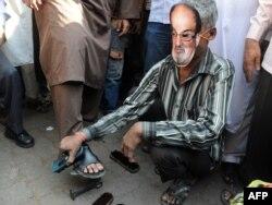 """Mumbayda Salman Rüşdiyə qarşı etiraz aksiyası. Onu """"ayaqqabı silən"""" kimi göstərirlər. 11 yanvar, 2012"""