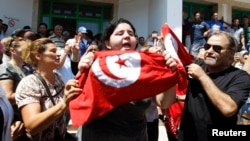 Assassinated Tunisian opposition politician Muhammad Brahmi's daughter Balkis (center) holds a Tunisian flag as she mourns his death in Tunis on July 25.