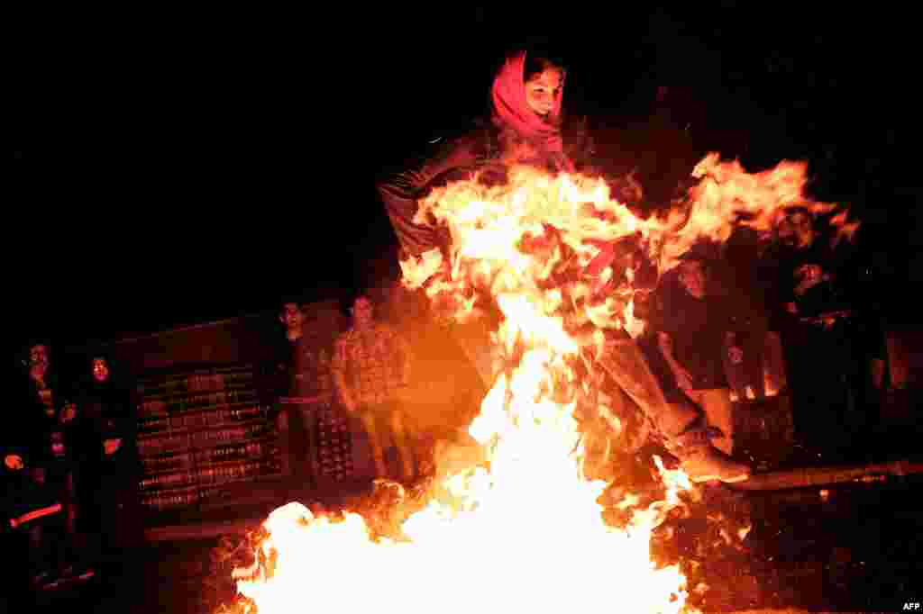 A woman jumps over a bonfire in southern Tehran during the Fire Feast held before Norouz celebrations. (AFP/Behrouz Mehri)