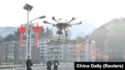 Китайские полицейские поднимают в воздух дрон для мониторинга ситуации на улицах города