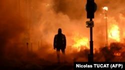 Наразылық акциясы кезінде көшедегі өрттің маңында тұрған адам. Бордо, Франция, 8 желтоқсан 2018 жыл.