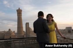 A young couple enjoy a summer sunset near the Kalyan Minaret in Bukhara in 2015.