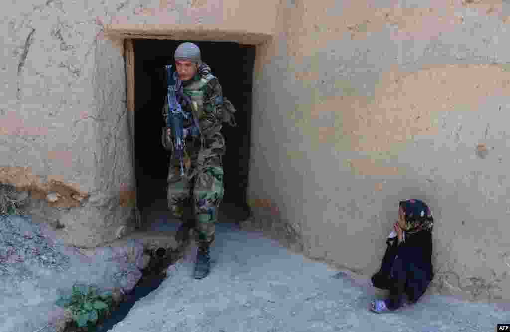 An Afghan girl watches an Afghan National Army (ANA) special-forces soldier as he patrols in the Gozara district of Herat. (AFP/Aref Karimi)