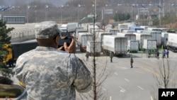 Военнослужащие США фотографируют южнокорейские грузовики, которых не пустили в Кэсон 3 апреля 2013 г.