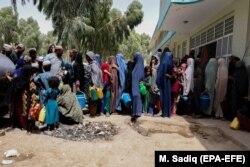 Familiile strămutate din zonele în care se desfășoară lupte între forțele de securitate afgane și talibani așteaptă ajutor în timp ce locuiesc în adăposturi temporare în Kandahar, 4 august 2021