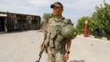 A Kyrgyz soldier stands guard near a burned border post in the village of Maksat in Batken Province on May 4.