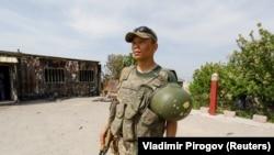 Кыргызский военнослужащий возле сгоревшего пограничного поста в селе Максат Баткенской области. 4 мая 2021 года.