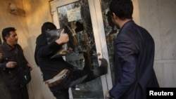 A protester kicks a door in the British Embassy compound in Tehran on November 29, 2011.