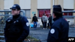 FILE: Policemen stand during the evacuation of a migrants and refugees camp in Franc.e