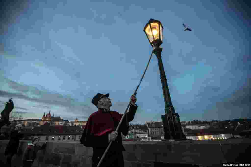 Lamplighter Jan Tater lights an antique gas lamp on Charles Bridge in Prague, (epa-EFE/Martin Divisek)