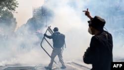 Gesturi ale protestatarilor care au fost nevoiți să se confrunte cu gaze lacrimogene la Paris de 1 Mai.